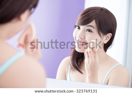 Beautiful Woman using cosmetic sponge on face with smile and look mirror. asian beauty - stock photo