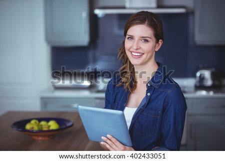 Beautiful woman using digital tablet in kitchen at home