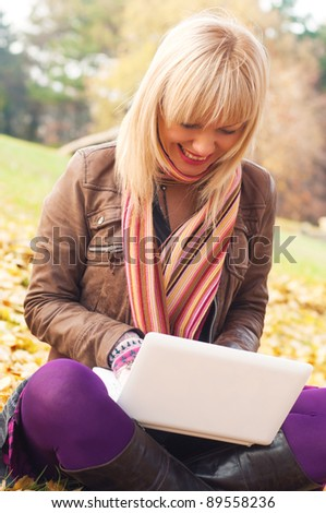 Beautiful woman using her laptop in park - stock photo