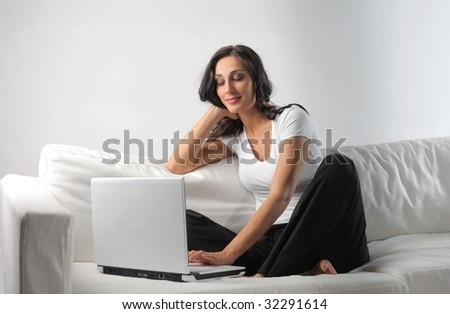 beautiful woman using laptop on a sofa - stock photo