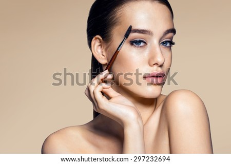 Beautiful woman using mascara / photos of appealing brunette girl on beige background