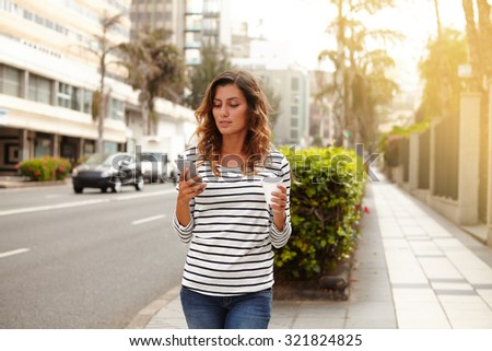 Beautiful woman using smart phone while walking on city avenue - focus on foreground - stock photo
