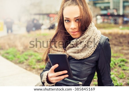 Beautiful woman using tablet computer on the street