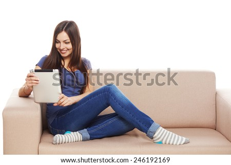 Beautiful woman using tablet sitting on sofa at home - stock photo