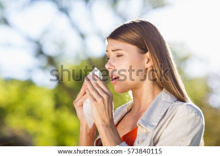 stock photo beautiful woman using tissue while sneezing in park 573840115
