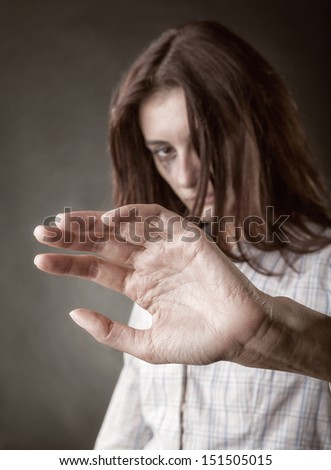 Beautiful woman victim of domestic violence and abuse. Focus on hand - stock photo