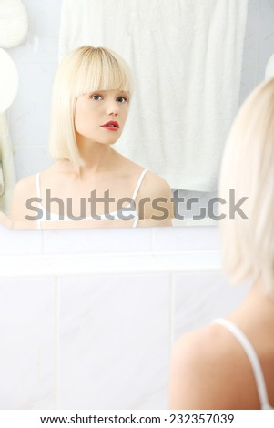 Beautiful woman viewing herself in the mirror. - stock photo