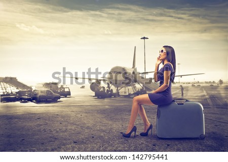 beautiful woman waits sitting on suitcase talking on the phone to start - stock photo