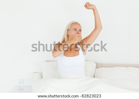 Beautiful woman waking up in her bedroom - stock photo