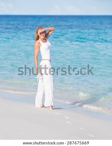 Beautiful woman walking along clean sandy coast in bright sunny day, spending summer vacation on beach resort on Maldives