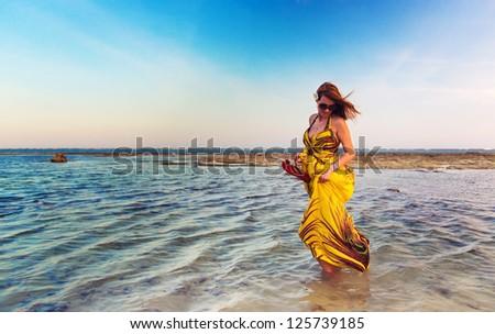 Beautiful woman walking in water wearing a yellow colorful dress - stock photo