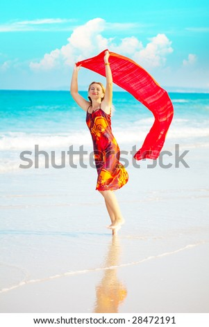 Beautiful woman walking near the ocean with red sarong - stock photo