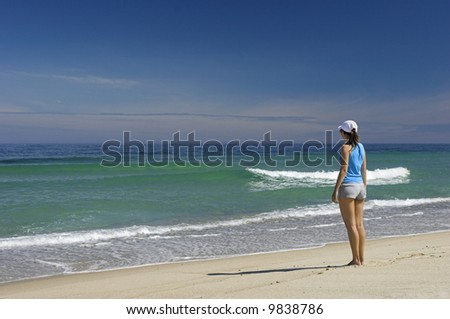 Beautiful woman walking on the beach feeling the breeze