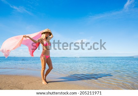 Beautiful woman walking on tropical beach with sarong blowing in the wind - stock photo