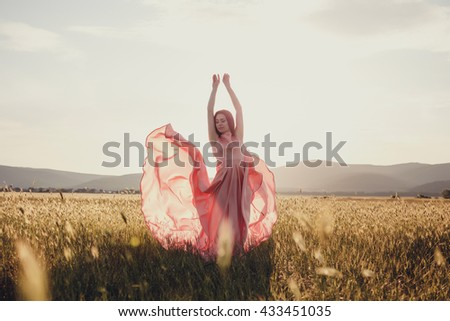 beautiful woman walking on wheat field before sunset. Cute lady walking through the meadow. - stock photo