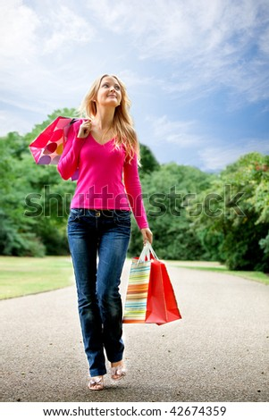 Beautiful woman walking with paper bags outdoors - stock photo