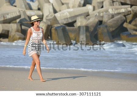 Beautiful woman walks along beach in swimsuit cover-up and hat - wind blowing hair  - stock photo