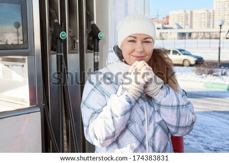 Beautiful woman warming hands in petrol station at winter - stock photo