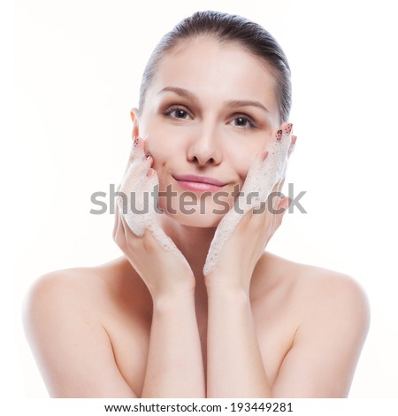 Beautiful woman washing her face - isolated on white - stock photo