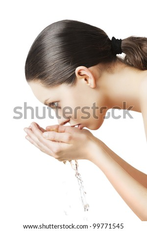 Beautiful woman washing her face isolated on white with wet hair and natural make up, she is in profile and birngs water to her mouth with both hands - stock photo