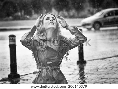 Beautiful woman wearing a coat posing in the rain. Happy long hair girl enjoying the rain drops in the park, outdoor shot. Attractive female relaxing in a rainy day. Black and white photo - stock photo