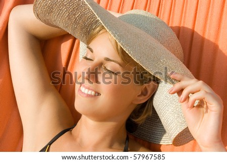 Beautiful woman wearing a hat lying in a hammock - stock photo