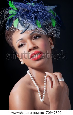 Beautiful woman wearing a retro style hat, isolated on black - stock photo