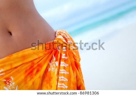 beautiful woman wearing a sarong at the beach - stock photo