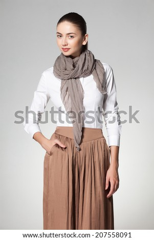 beautiful woman wearing a scarve on grey background - stock photo