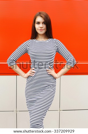 Beautiful woman wearing a striped dress in city over red  - stock photo