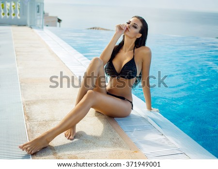 Beautiful woman wearing black bikini by the pool in summer scenery - stock photo
