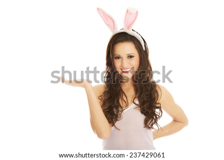 Beautiful woman wearing bunny ears and presenting a copyspace - stock photo