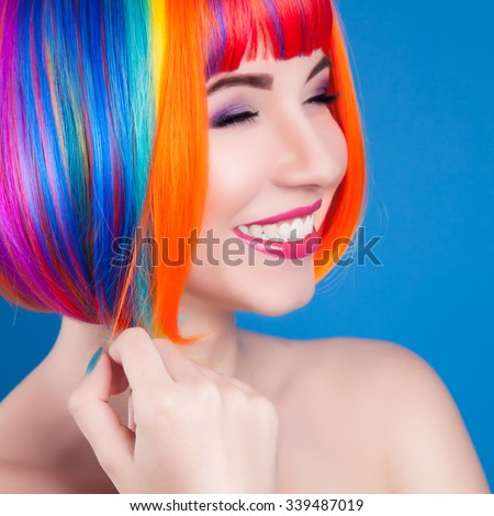 beautiful woman wearing colorful wig against blue background - stock photo