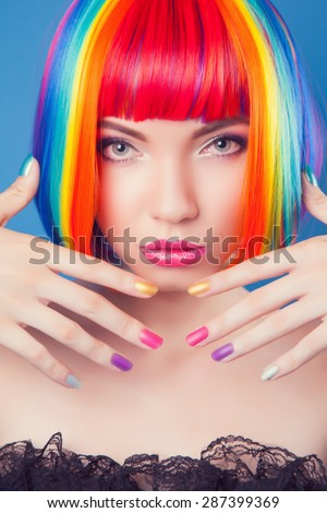 beautiful woman wearing colorful wig and showing colorful nails against blue background - stock photo