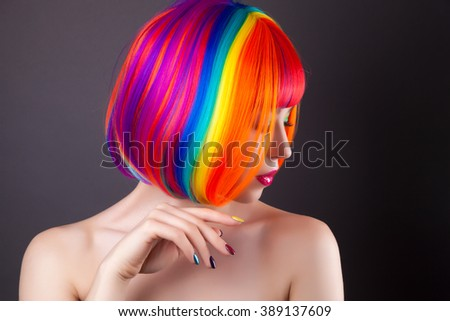 beautiful woman wearing colorful wig and showing colorful nails against gray background - stock photo