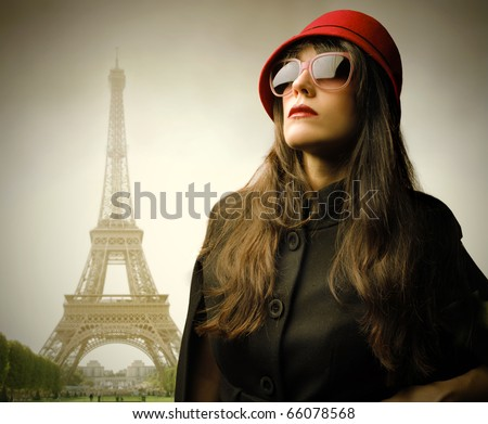 Beautiful woman wearing fashion sunglasses and hat with Eiffel Tower on the background - stock photo