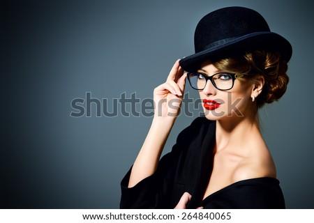 Beautiful woman wearing glasses and bowler hat. Retro style. Beauty, fashion. Make-up. Optics, eyewear.  - stock photo