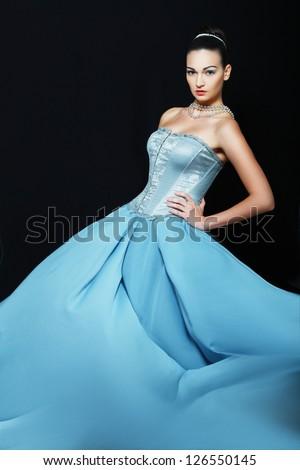 Beautiful woman wearing in wedding dress posing over black background - stock photo