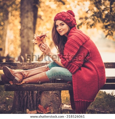 Beautiful woman wearing knitted coat in autumn park  - stock photo