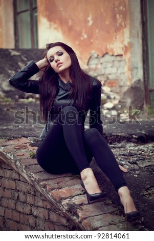 beautiful woman wearing leather jacket sitting on ruins - stock photo