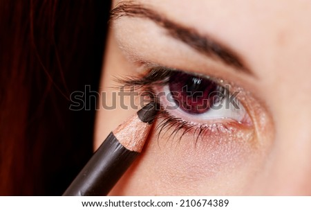 beautiful woman wearing makeup for red eyes with eyeliner - stock photo