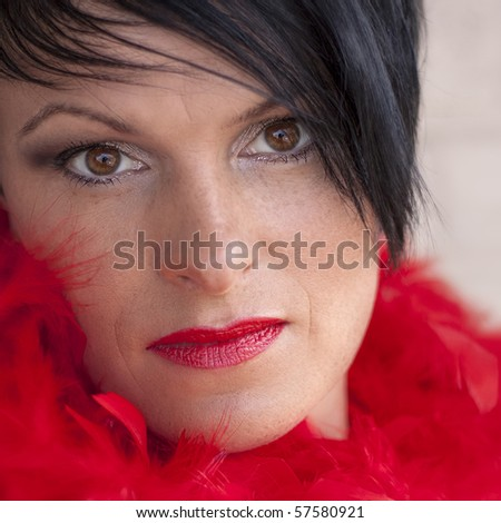 Beautiful woman wearing red feathers - stock photo
