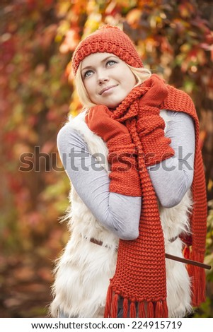 beautiful woman wearing red hat gloves and scarf against colorful autumn tree - stock photo