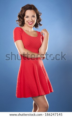 beautiful woman wearing red summer dress on blue background - stock photo