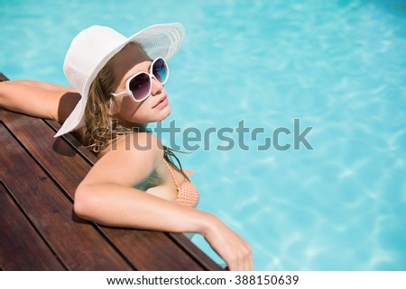 Beautiful woman wearing sunglasses and straw hat leaning on wooden deck by poolside on a sunny day