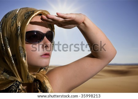 Beautiful woman wearing sunglasses head covered with scarf over a desert background - stock photo