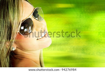 Beautiful woman wearing sunglasses â?? over a green background - stock photo