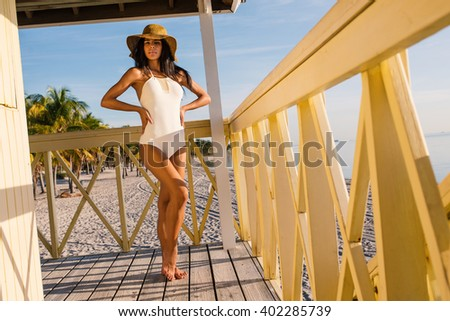 Beautiful woman wearing swimsuit relaxing on a Lifeguard tower in the beach of Crandon Park in a sunny day. Key Biscayne. Miami, florida. - stock photo