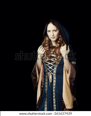 Beautiful woman wearing vintage medieval dress with hood in gothic church - stock photo