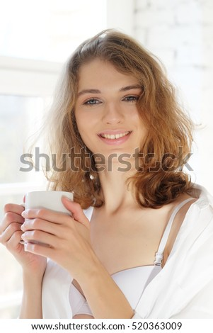 Beautiful woman wearing white lingerie drinking coffee in the mo